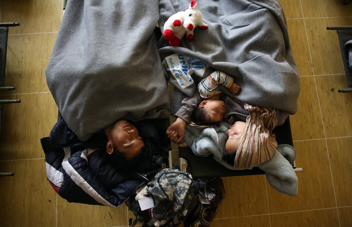 A family sleeping in blankets from the United Nations High Commissioner for Refugees (UNHCR), at the Refugee Aid Center in Šid, Serbia